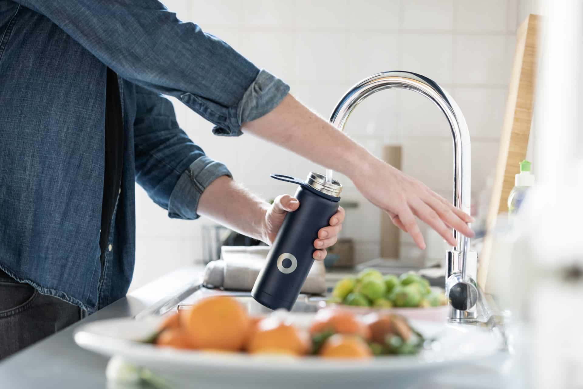 A person filling up a water bottle using a kitchen faucet
