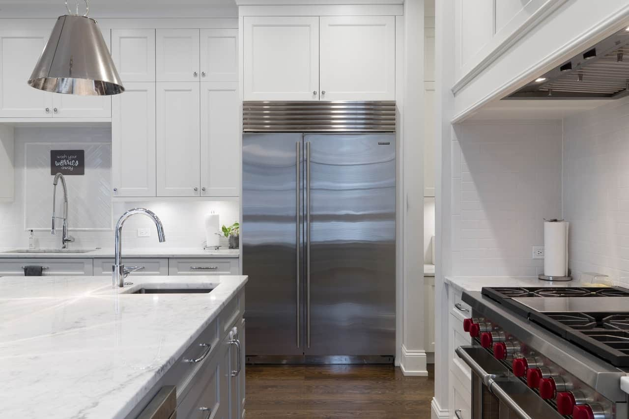 A stainless steel double refrigerator in a large kitchen