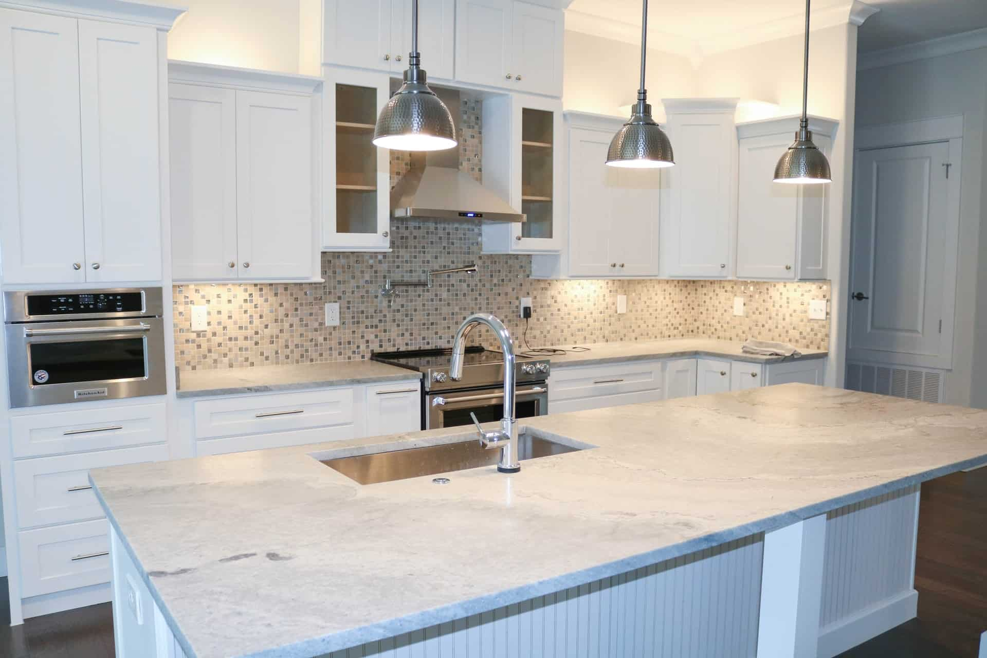 A white modern kitchen with hanging lights, a modern faucet and sink