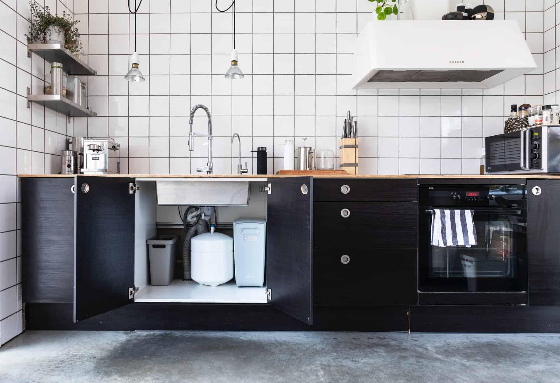 Garbage disposal under a kitchen sink in a clean kitchen