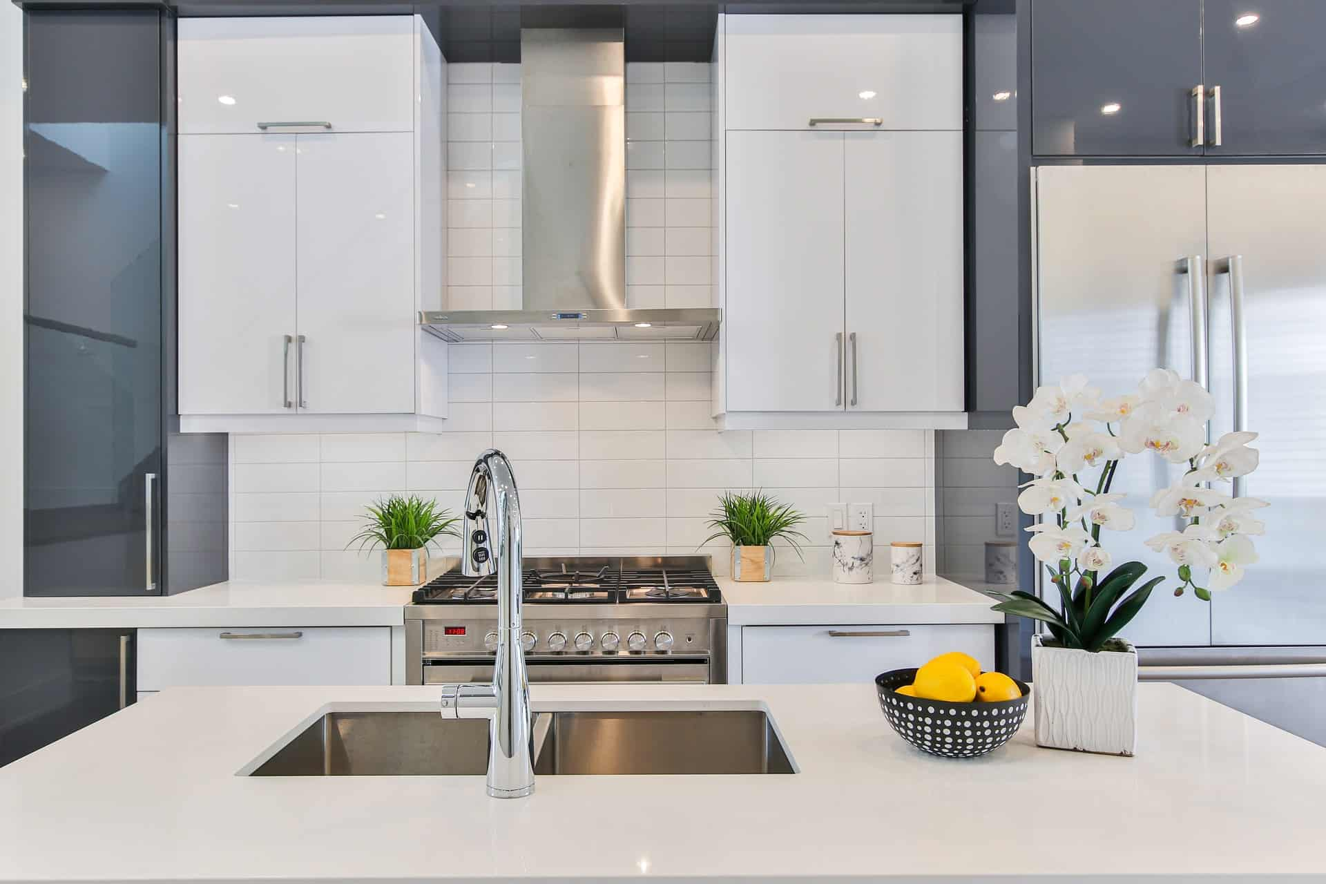 A delta kitchen faucet in a large white kitchen