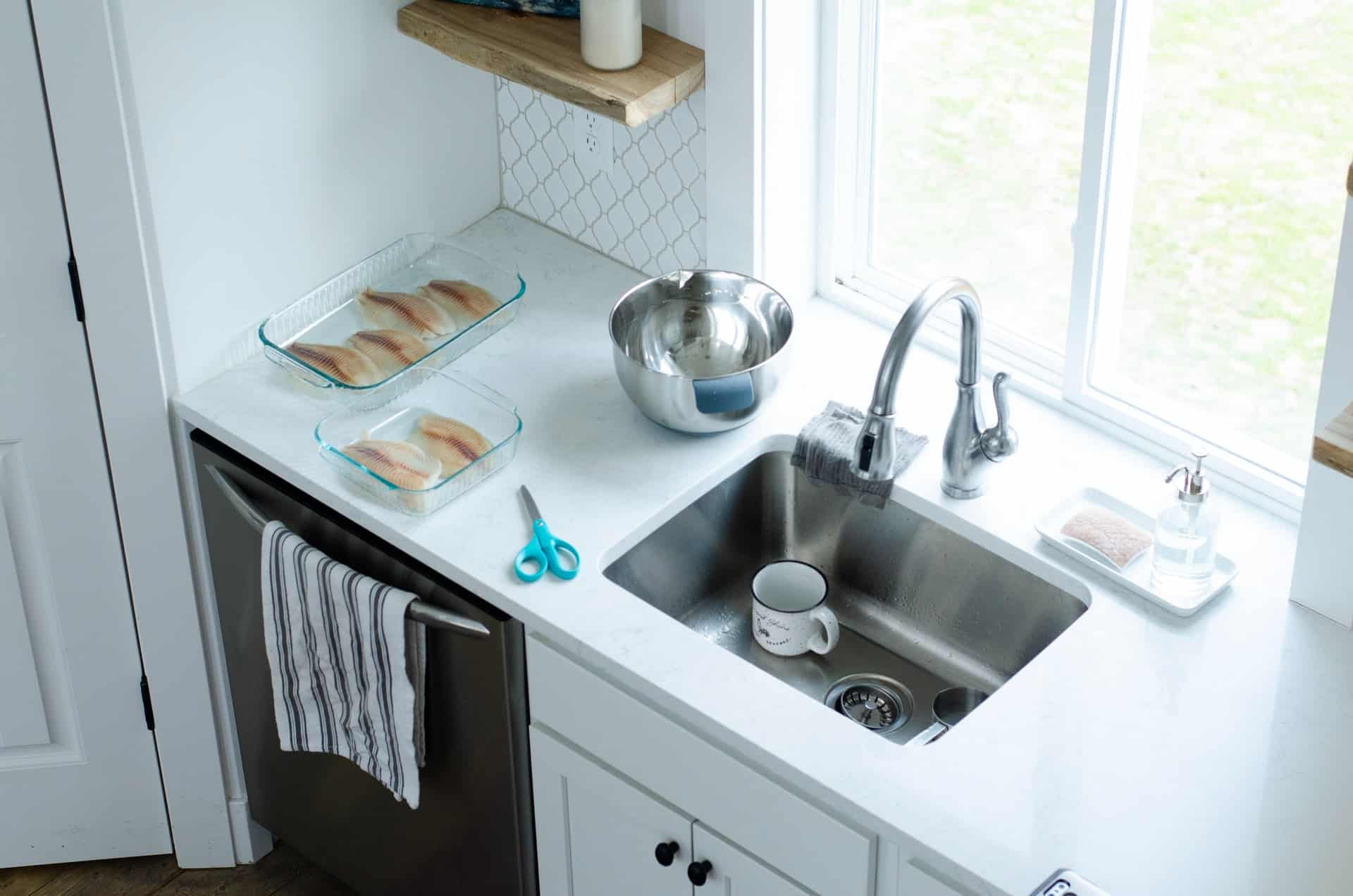 Stainless steel sink in a small white kitchen