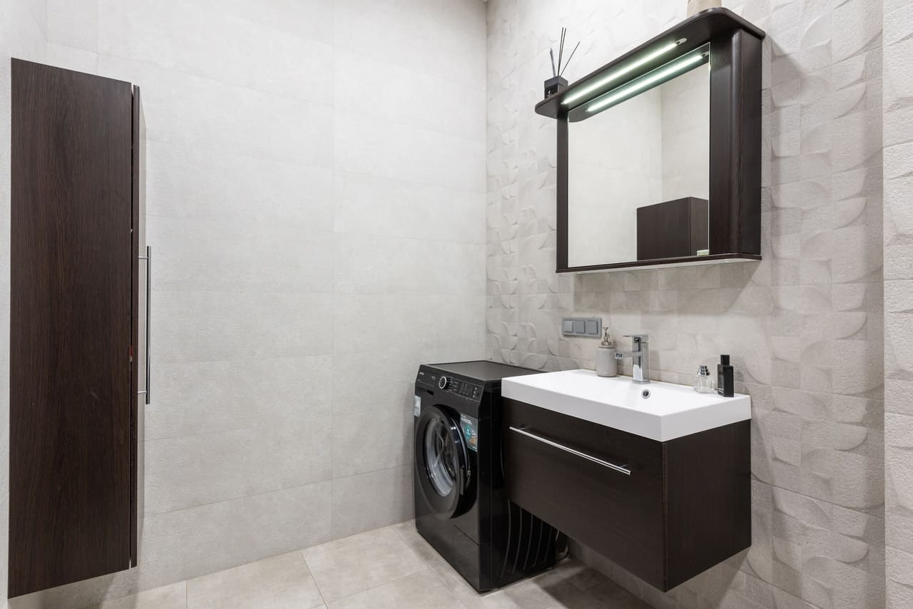 Utility sink with a faucet and washing machine