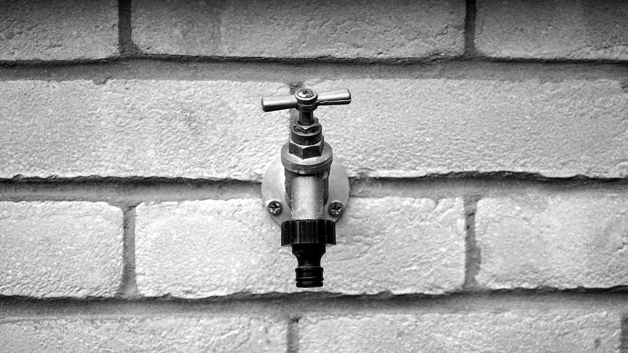 Outdoor faucet attached to a brick wall