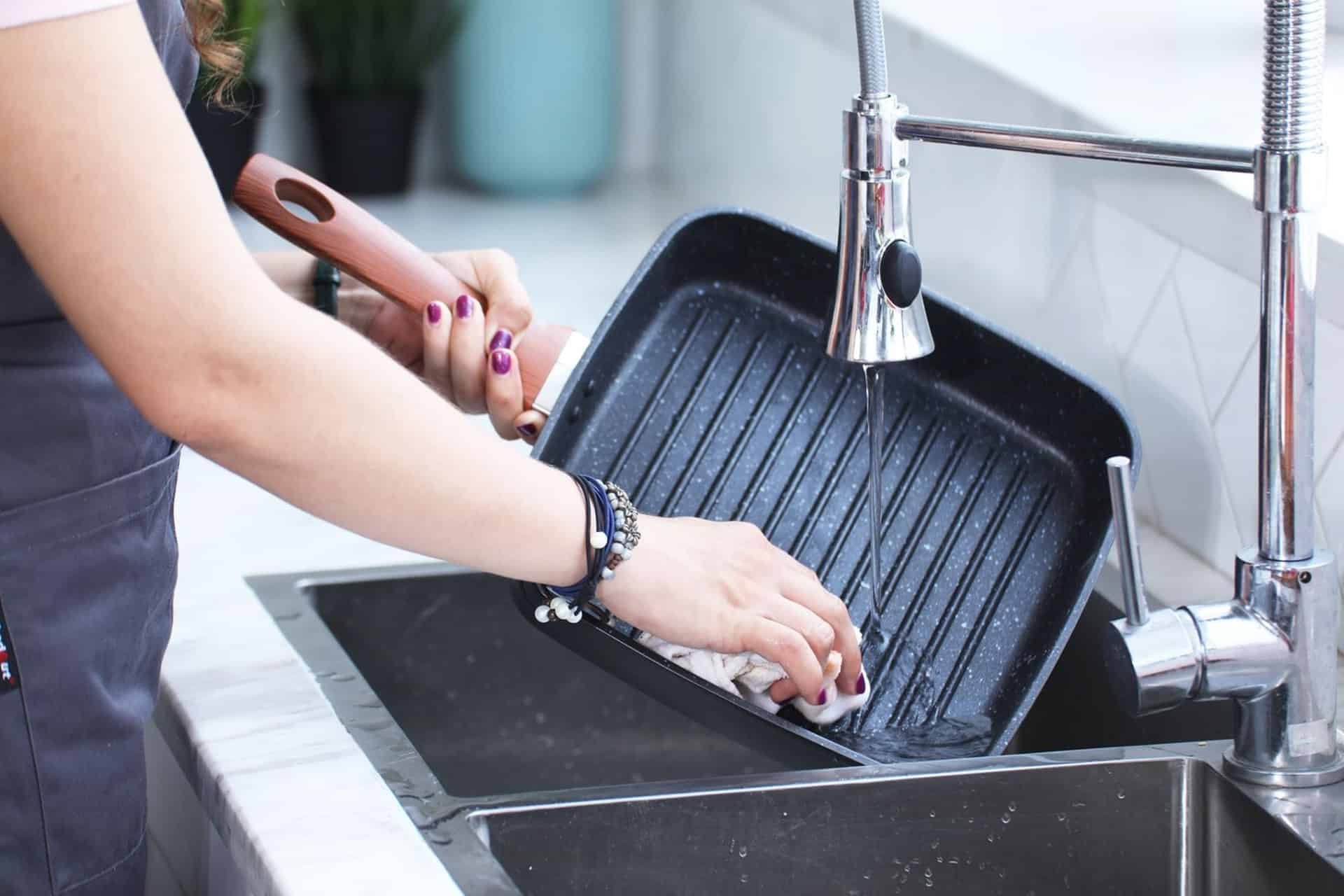 Best Commercial Kitchen Faucet cleaning a cast iron griddle pan
