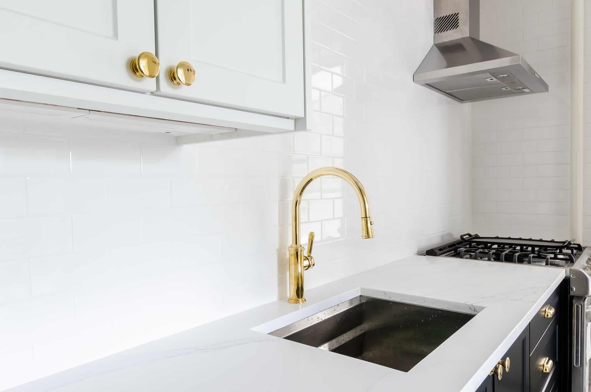 Gold Kraus faucet in a white kitchen