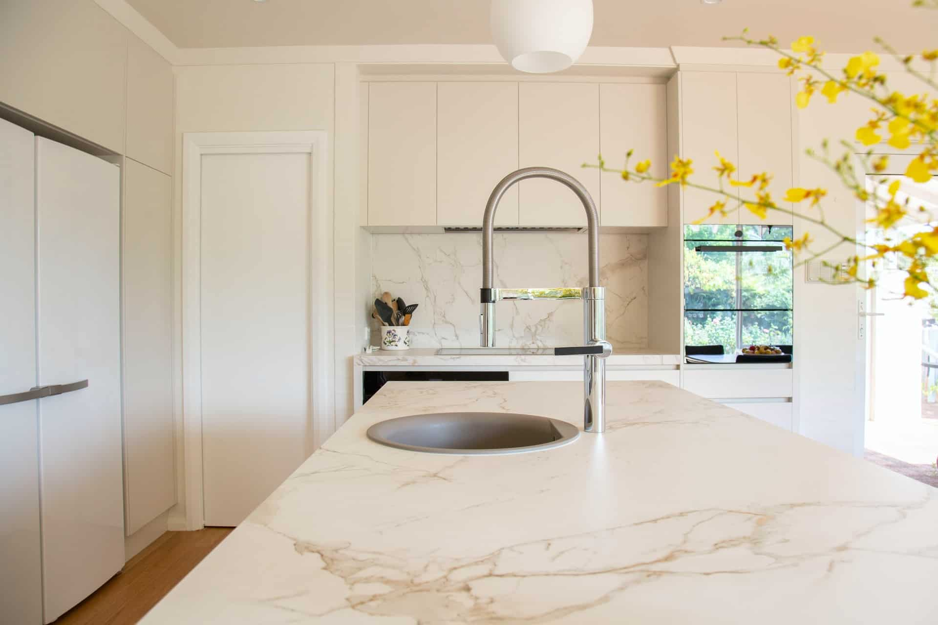 pull down kitchen faucet on a marble countertop in a kitchen