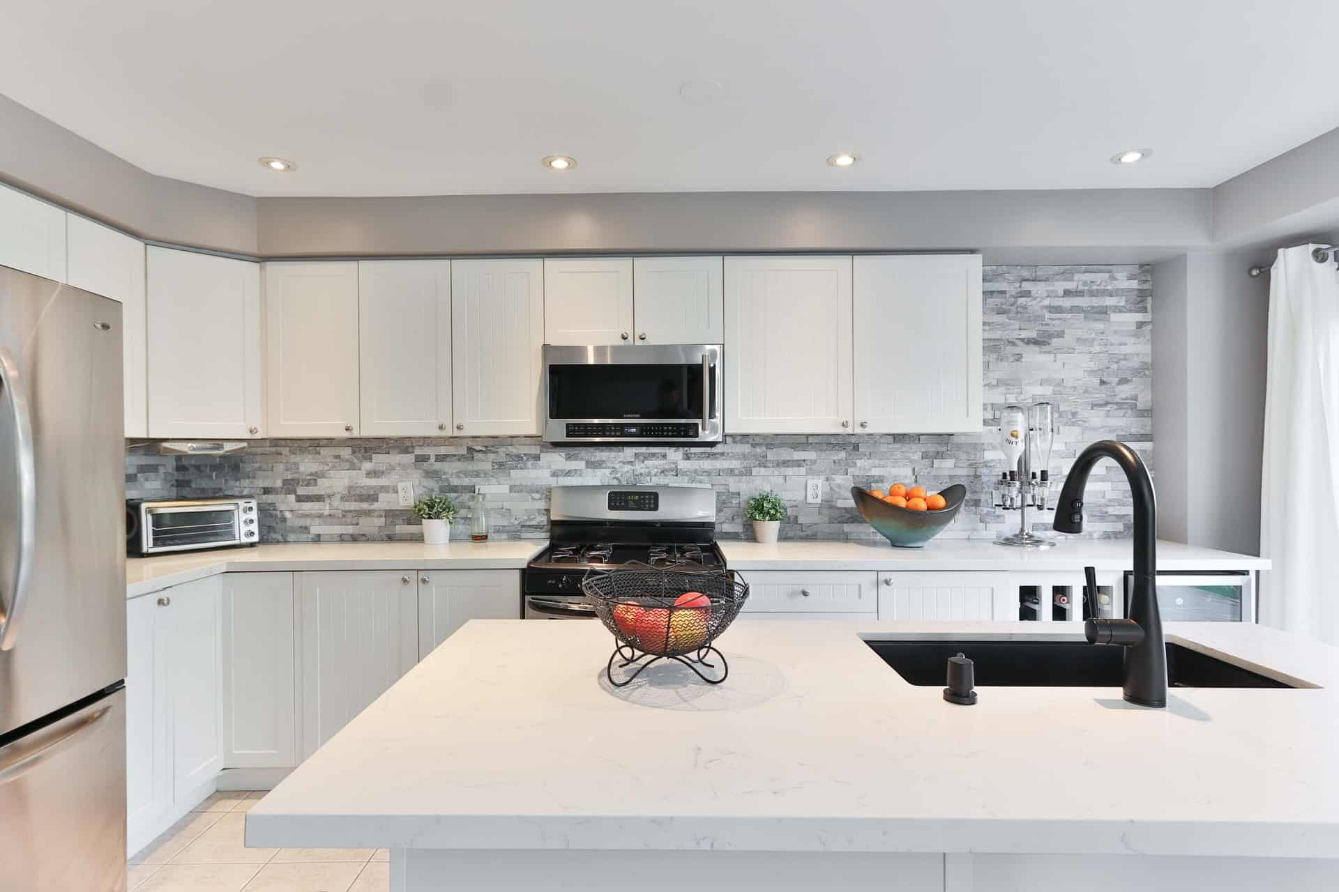 A black faucet made from the USA in a white sleek kitchen
